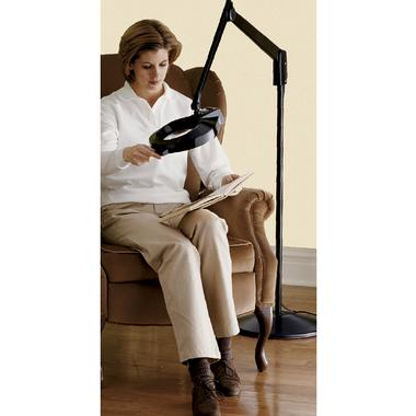 Woman sitting on a couch, reading a book using the Floor Standing Magnifier Lamp, which resembles a giant magnifying glass