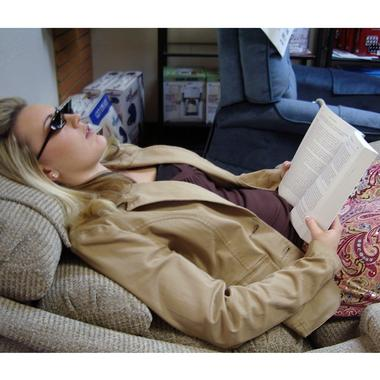 Woman wearing Deluxe Prism Glasses to read a book while lying down on a reclining chair