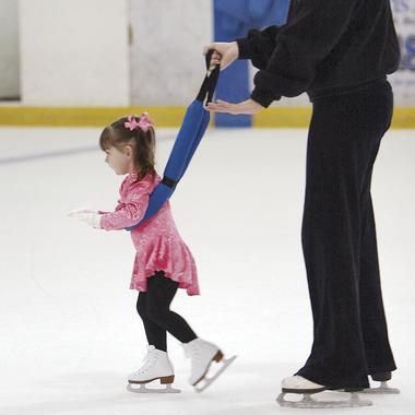 A young girl ice-skates while wearing the Walk-O-Long, which resembles a leash wrapped around her waist, held by an adult