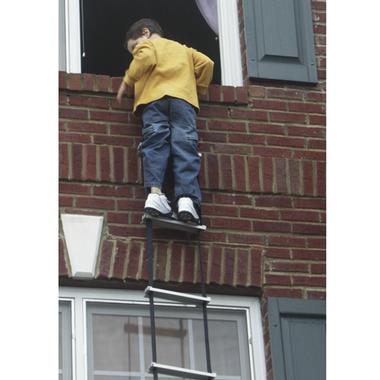 A young boy climbs out of a high window of a house using the Permanent Escape Rescue Ladder