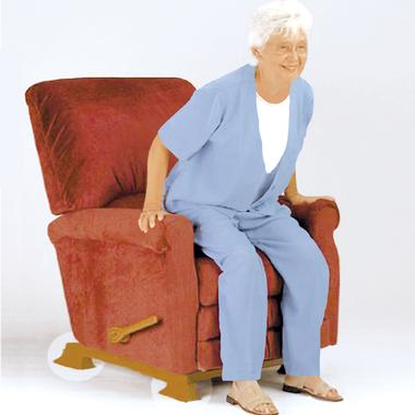 Elderly woman lowers herself onto a recliner raised off the floor by Recliner Risers, a set of wooden chair 'legs'