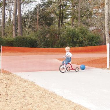 A young boy rides a tricycle in front of the Driveway Net, which is blocking the end of a driveway and preventing a ball from rolling into the street