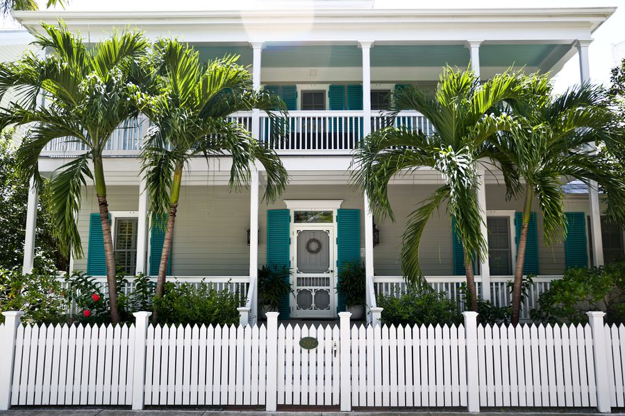A home in Key West, the outside is white with teal accents and palm trees out front.