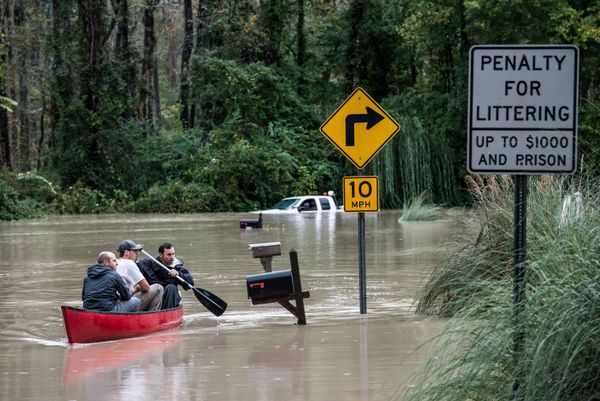 Will Brennan, Matt Talley and Tyler Bahnmuller take a canoe to investigate their homes following flooding in the area October 5, 2015 in Columbia, South Carolina