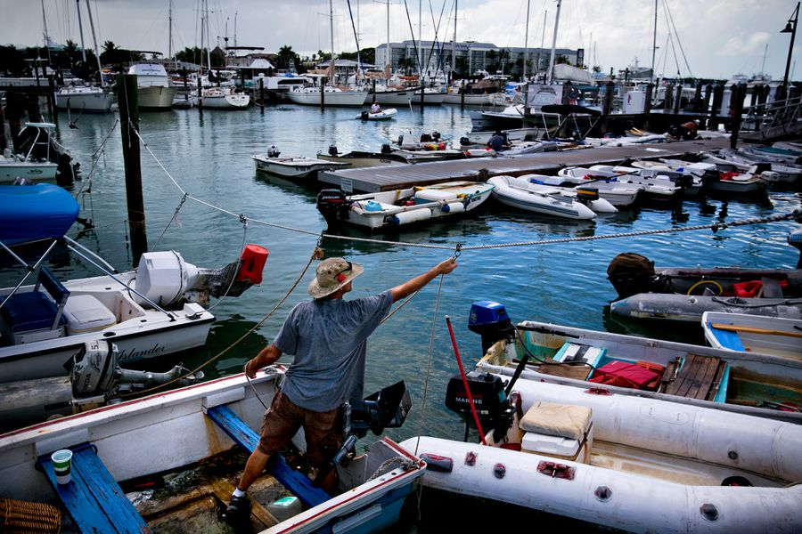 A Fisherman works on his boat surrounded by many other boats near Schooner Wharf.