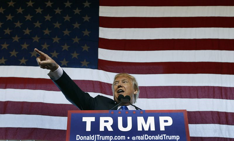 Donald Trump speaks at a campaign rally in front of a giant American flag.