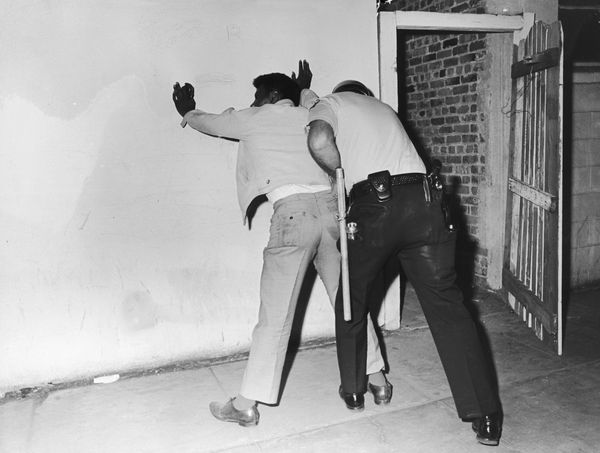 A police frisking of an African-American man during the Watts riots