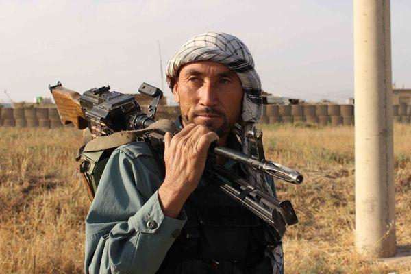 An Afghan policeman holds a gun on his sholder a day after Taliban insurgents overran Kunduz