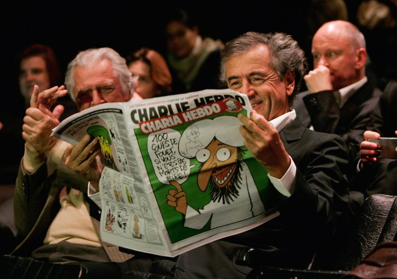 French philosopher Bernard-Henri Levy reads a 2011 issue of Charlie Hebdo (Franck Prevel/Getty)