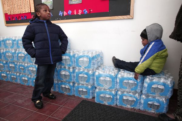 Justin Roberson (L), age 6, of Flint, Michigan and Mychal Adams, age 1, of Flint wait on a stack of bottled water.
