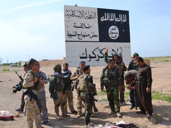 Iraqi Kurdish Peshmerga fighters stand next to an ISIS sign at the entrance to the Iraqi town of Hawija, near where the hostage rescue raid took place.
