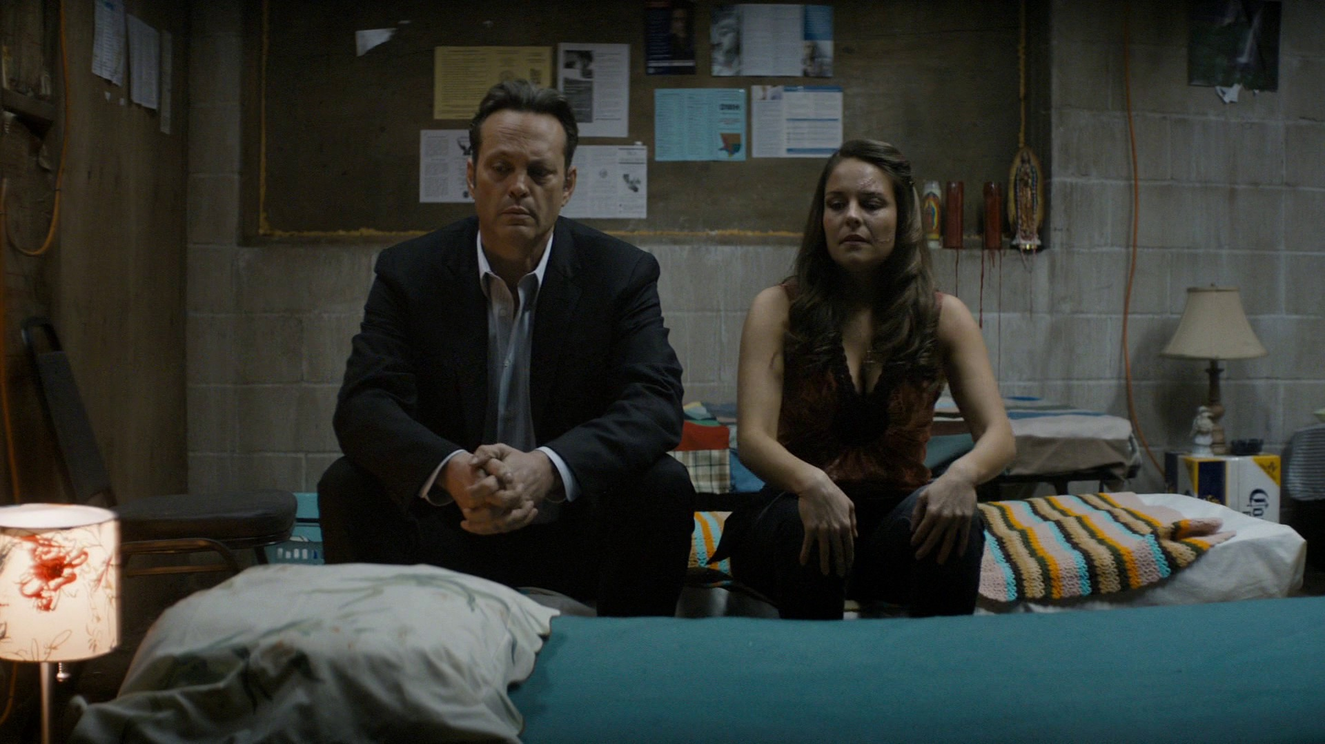 Felicia and Frank sit on a bed