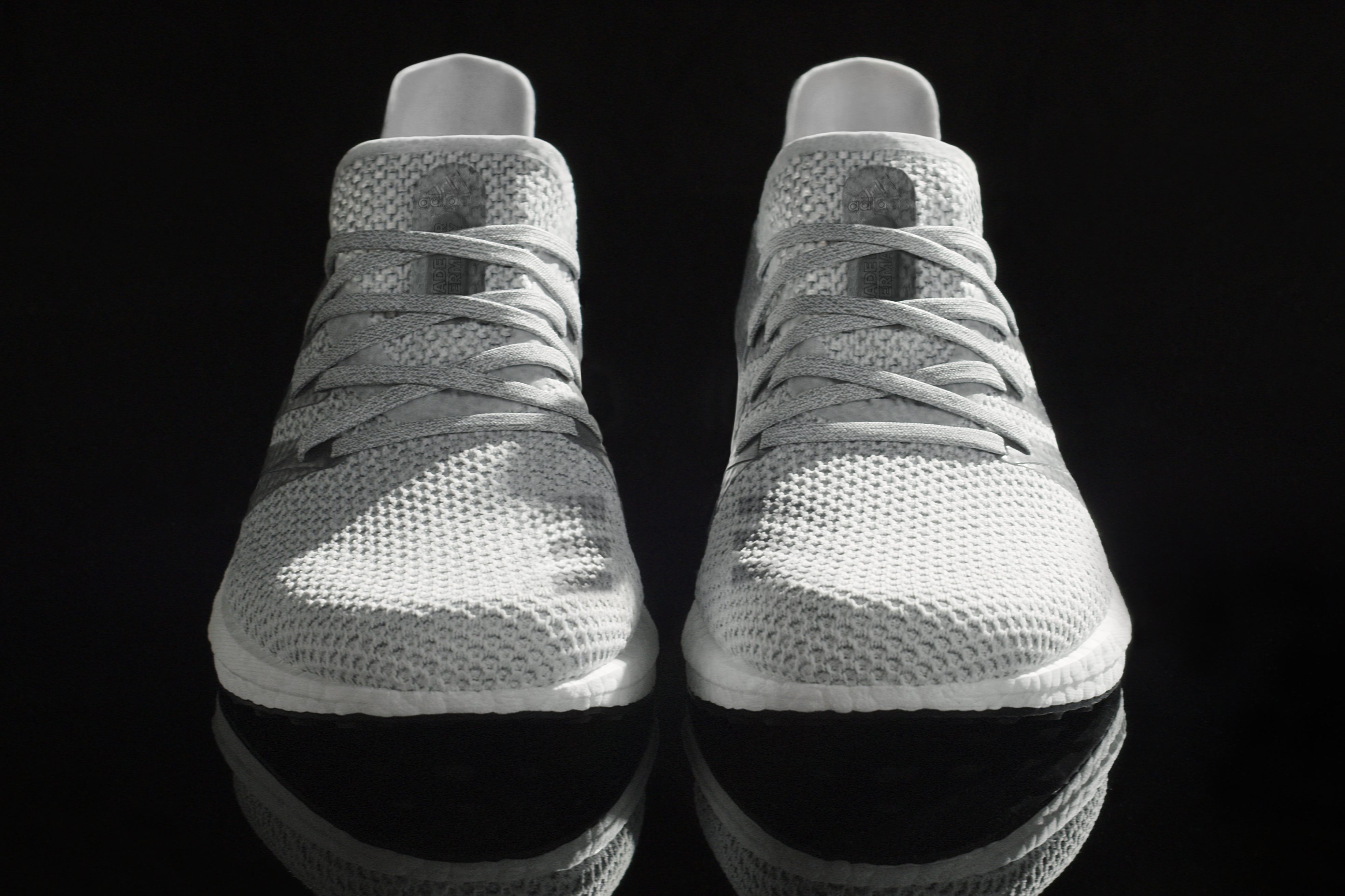 A pair of white and grey sneakers, seen from the front, on a black background. The laces are part of the shoe, you don't have to tie them. They are covered in a sort of mesh.