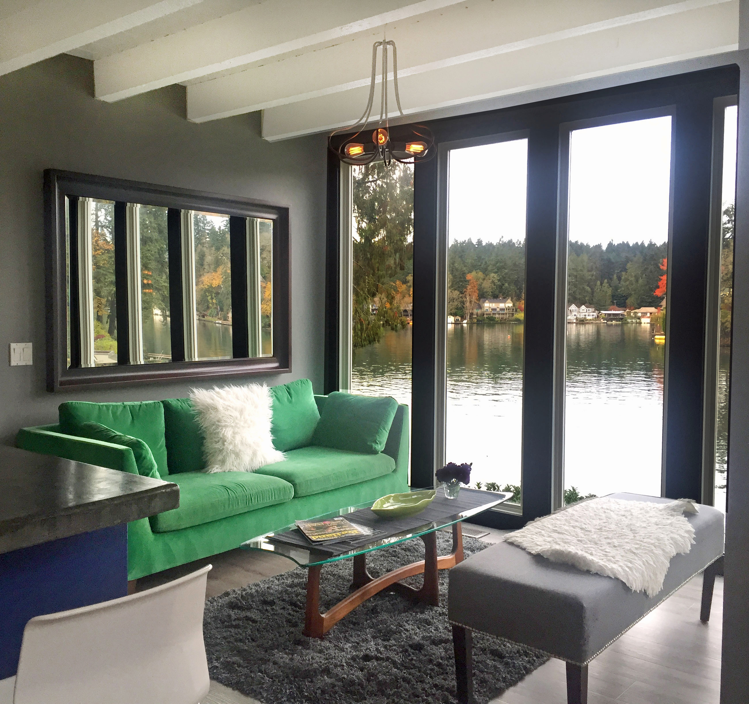 A bright green couch in a living room with dark grey walls and floorto colors cool paint to